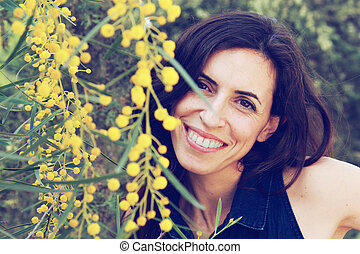 Portrait of smiling woman outdoors with yellow flowers