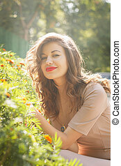 woman poses on background bed of flowers
