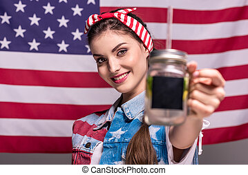 portrait of smiling woman showing detox drink in hand with American flag on background