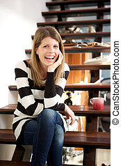 smiling woman sitting on stairs at home