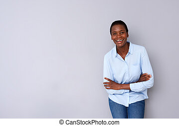 smiling woman standing with arms crossed against gray background