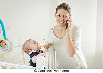 Portrait of smiling woman talking by phone while feeding her baby son