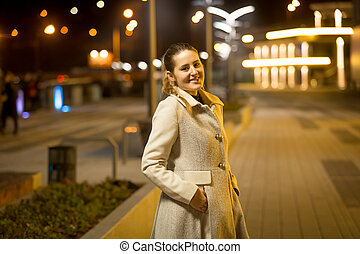 Portrait of smiling woman walking on street at night