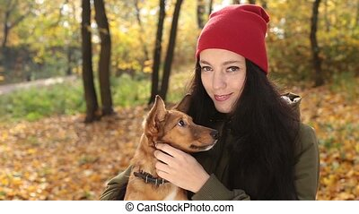 Portrait of smiling woman with her dog in autumn