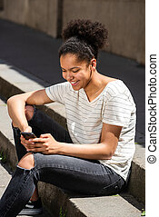 smiling young african american girl sitting outside looking at cellphone