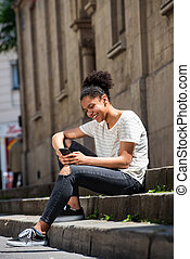 smiling young african american girl sitting outside looking at mobile phone