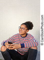 smiling young african american girl sitting with cellphone
