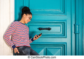smiling young african american girl standing with cellphone