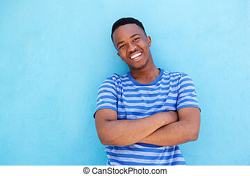 smiling young african american man leaning against blue wall