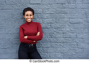 smiling young african american woman against gray wall