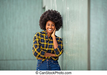 smiling young african american woman leaning against wall