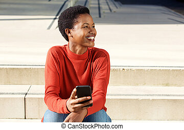 smiling young african american woman sitting outside with mobile phone