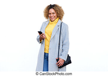 smiling young african american woman smiling with mobile phone and purse by white wall