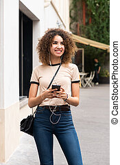 smiling young african american woman standing with mobile phone and earphones in city