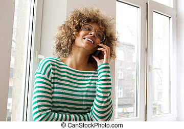 smiling young african american woman talking on cellphone by window