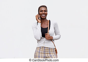 smiling young african american woman talking on mobile phone against isolated white background