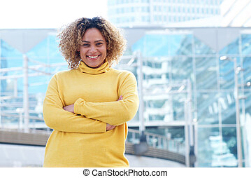 smiling young african american woman with curly hair and arms crossed in city