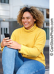 smiling young african american woman with mobile phone in city