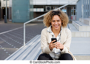 smiling young african american woman with phone outside