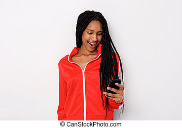 smiling young african woman holding mobile phone with surprised expression