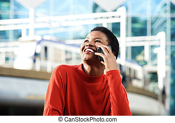 smiling young african woman talking on cellphone in city