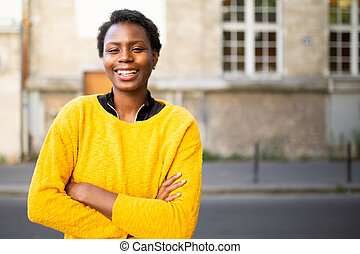 smiling young african woman with arms crossed in city