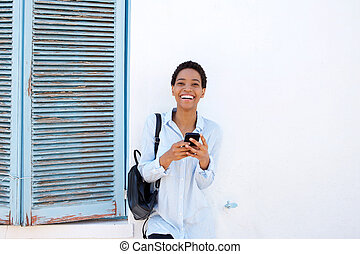 smiling young african woman with mobile phone and bag
