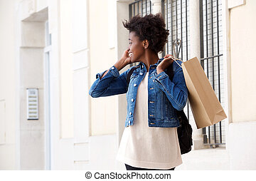 african woman with shopping bag talking on cellphone and looking back