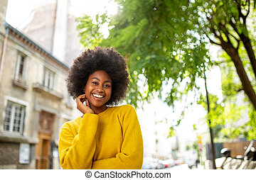 smiling young afro american woman standing outside
