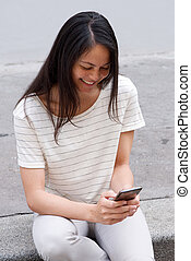 smiling young asian woman using cellphone outdoors