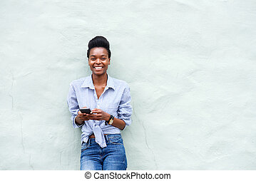 smiling young black woman holding cellpone