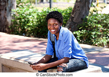 smiling young black woman sitting outside with a mobile phone