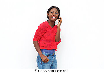 smiling young black woman talking on mobile phone against isolated white background