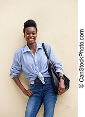 smiling young black woman with handbag