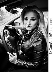 Portrait of smiling young blond woman in car.