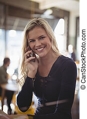 Portrait of smiling young blond woman talking on mobile phone
