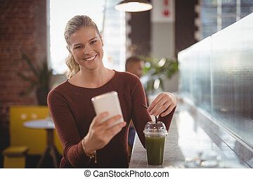 Portrait of smiling young blond woman using smartphone while sitting with drink