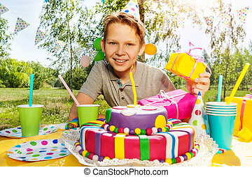 Portrait of smiling young boy with birthday gifts