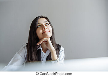 Portrait of smiling young business woman dreaming in office.