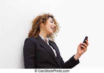 smiling young business woman looking at mobile phone