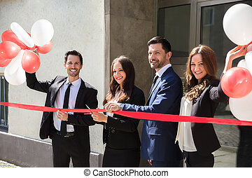 Businesspeople Cutting Red Ribbon