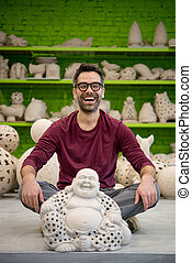Portrait of Smiling Young Ceramist in the Bright Modern Ceramic Workshop Sitting Next to Sculpture. Small Business Concept.