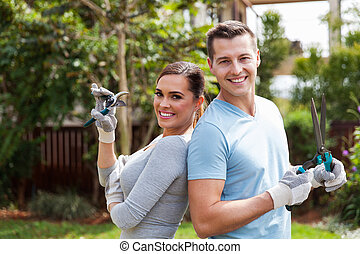 young couple standing in home garden