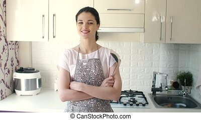 Portrait of smiling young housewife in modern kitchen -...