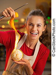 Portrait of smiling young housewife removing orange peel