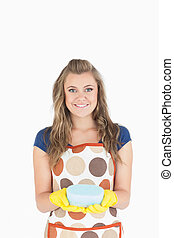 Portrait of smiling young maid holding sponge