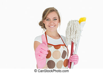 Portrait of smiling young maid with cleaning supplies gesturing thumbs up sign over white background