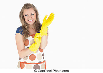 Portrait of smiling young maid with rubber gloves