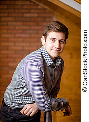 Smiling Young Man Leaning Against Brick Wall