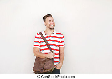 smiling young man standing against white wall with bag